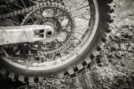 Rear wheel of sport bike on dirty motocross road photo