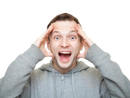 cara sorprendida: Hombre cauc�sico joven deportiva feliz sostiene la cabeza y se r�e. Foto de archivo