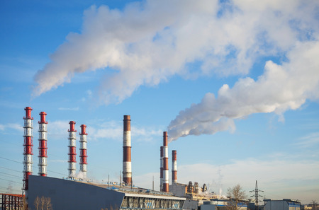 Industrial landscape  Power plant tubes with smoke above blue sky photo