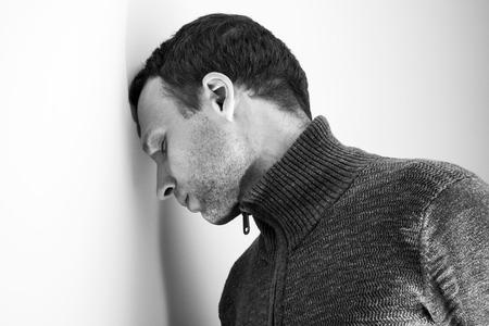 hombre caucasico: Hombre cauc�sico joven triste apoy� la cabeza en la pared blanca