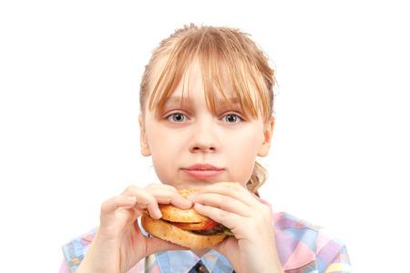 Little blond girl eats hamburger  Portrait isolated on white photo