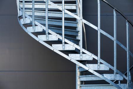 Fragmetn of modern metal spiral staircase above dark gray wall photo