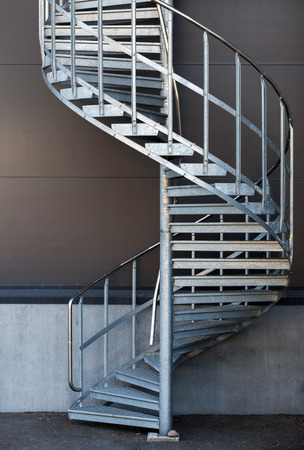 Modern metal spiral staircase above dark gray wall Stock Photo