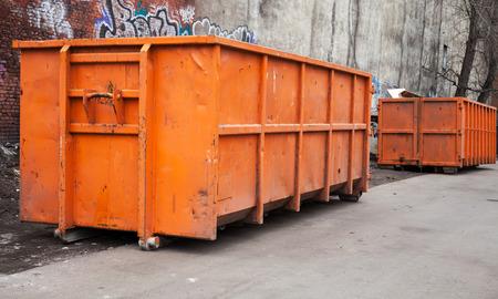 saltar: Contenedores grandes de basura de metal de color naranja en la ciudad