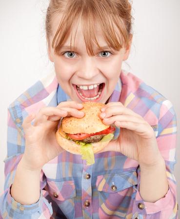 Little blond smiling girl eats hamburger above white wall photo
