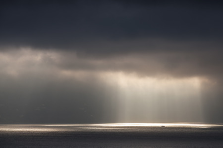 Bright sunlight goes through dark stormy clouds  Tangier bay, Morocco photo