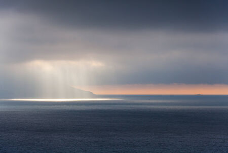 Bright sunlight goes through stormy clouds  Tangier bay, Morocco photo