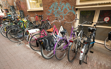 AMSTERDAM, NETHERLANDS - MARCH 19, 2014  Different bicycles stand on a parking place in Amsterdam