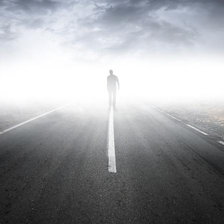 caminar: Asphalt perspectiva de la carretera con el hombre caminando en la niebla Foto de archivo