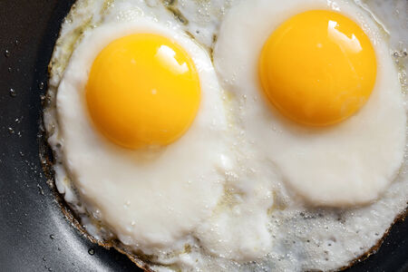 Macro photo of two scrambled eggs in black frying pan photo