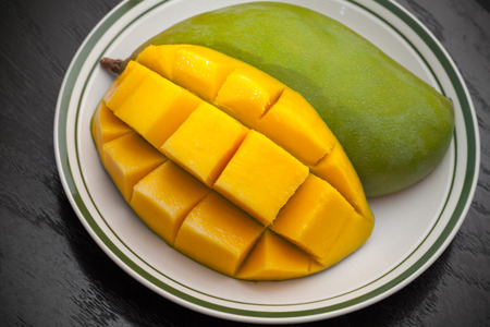 mangoes: Yellow cubes sliced mango on white plate