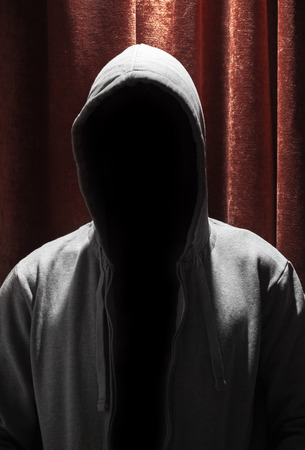 Portrait of Invisible man in the hood with red curtain background photo