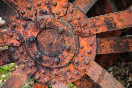 Closeup photo of old red rusted tractor wheel photo