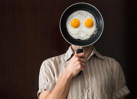 Portrait des jungen Mannes hinter schwarzen Bratpfanne mit Eiern krabbelte