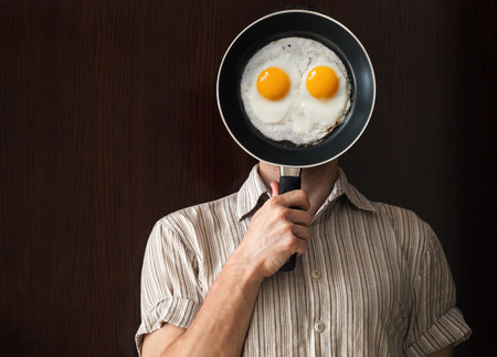 behind: Young man portrait behind black frying pan with scrabbled eggs
