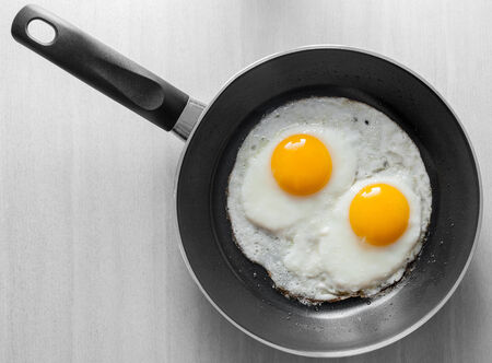 Two scrambled eggs in black frying pan on white wooden table photo