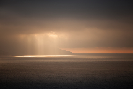 Bright sun lights go through dark stormy clouds. Tangier bay, Morocco photo