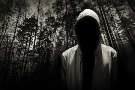 Portrait of dangerous man hiding under the hood in the forest Stock Photo