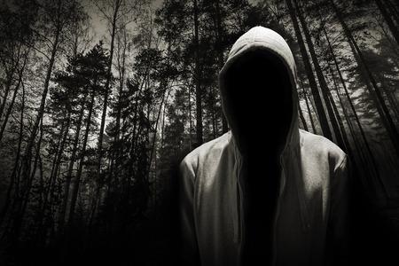 Portret van gevaarlijke man verstopt onder de kap in het bos