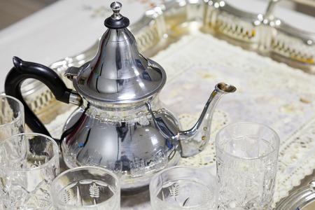 Arabic tea theme. Metal teapot with glasses photo