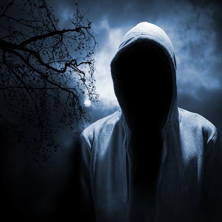 sudadera: Hombre peligroso esconderse debajo de la capilla en el bosque de la noche oscura Foto de archivo