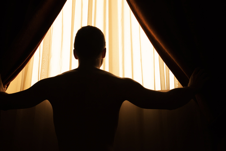 black out: Man in dark room opens curtains on window to the morning sunlight Stock Photo