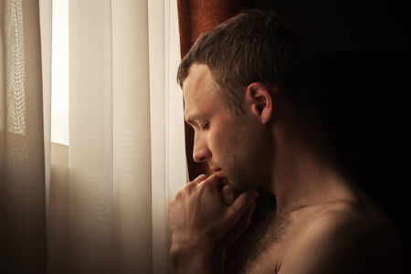 Young Caucasian man with closed eyes near the window photo