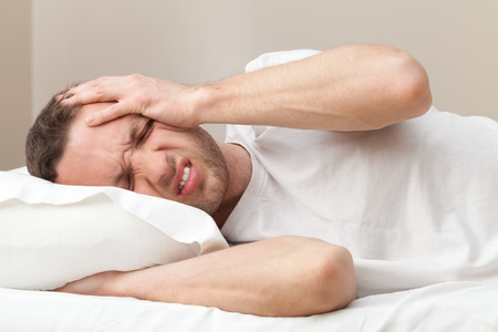 Portrait of Young Caucasian man in bed with headache  photo
