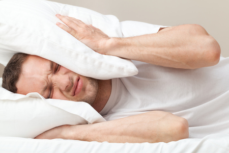 Portrait of dissatisfied Young Caucasian man in bed Stock Photo