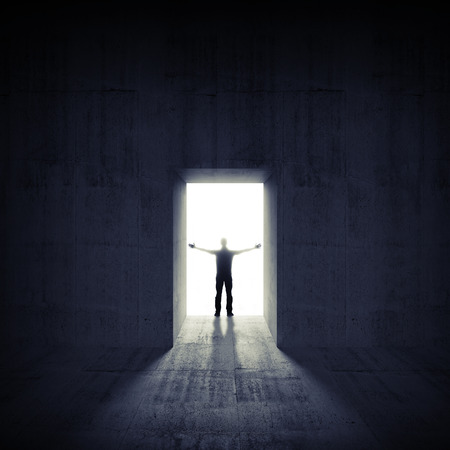 Abstract dark concrete interior with glowing door and man silhouette photo