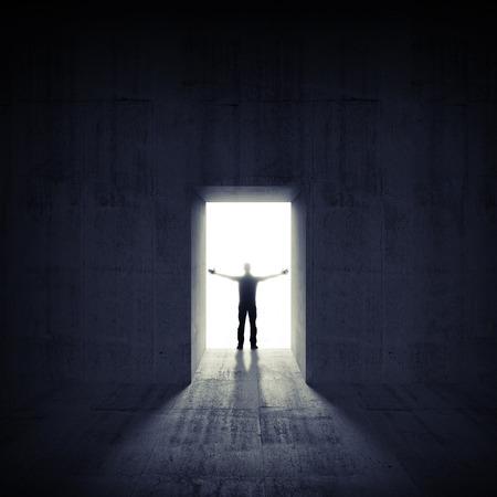 Abstracte donkere betonnen interieur met gloeiende deur en man silhouet