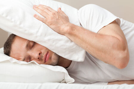 Portrait of Young Caucasian man in bed hiding from noise photo