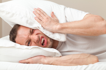 Portrait of Young Caucasian man in bed angry about noise  photo