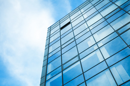building business: Modern office building wall made of steel and glass with blue sky