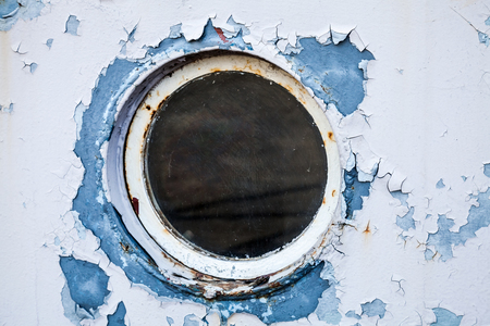 Round porthole in white and blue ship wall photo