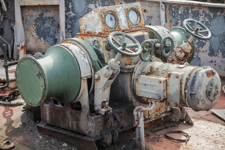 Rusted bow anchor winch on abandoned ship Stock Photo