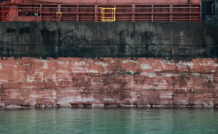 Black and red cargo ship hull side texture and water photo