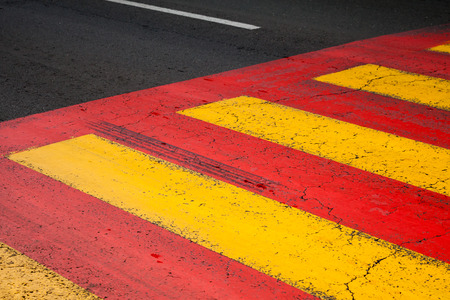 Pedestrian crossing road marking with yellow and red lines on asphalt photo