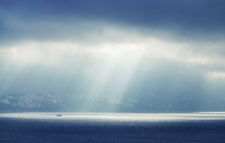 Bay of Tangier, Morocco. Sunlight goes through stormy clouds photo