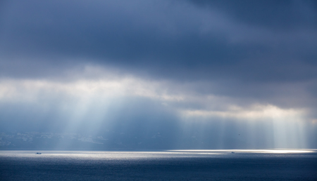 Sunlight goes through dark clouds. Bay of Tangier, Morocco photo