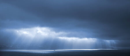 Sunlight goes through blue stormy clouds. Bay of Tangier, Morocco photo