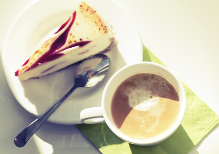 Cup of cappuccino coffee and cheesecake, vintage toned photo photo