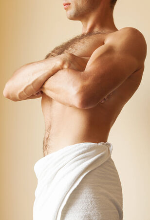 Strong young Caucasian man torso with white towel photo