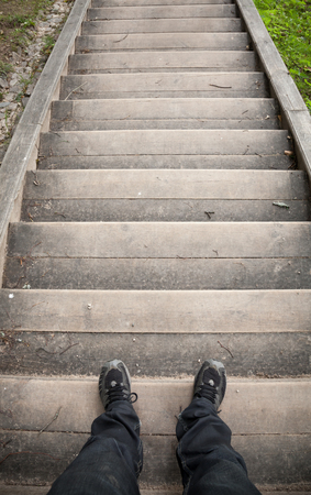 Looking down on a male legs and wooden stairway photo