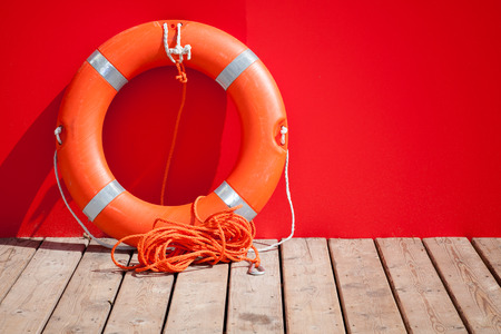 Lifebuoy stands on wooden floor nearby red wall of lifeguard station photo