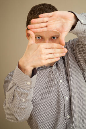 Young Caucasian man looks through hands frame, studio portrait  photo