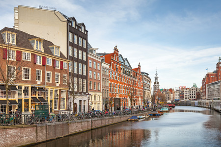 AMSTERDAM, NETHERLANDS - MARCH 19, 2014: Living houses along the canal embankment in spring day. Ordinary people walk on the coast