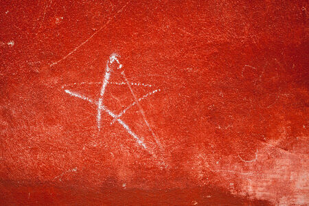 Red concrete wall with plastering and star sign photo