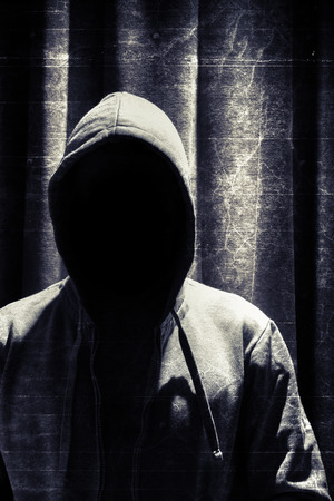 incognito: Portrait of incognito man under hood with grunge curtain background