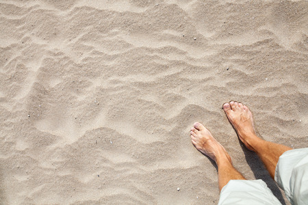 white sand: Legs of Young Caucasian man standing on a sandy beach